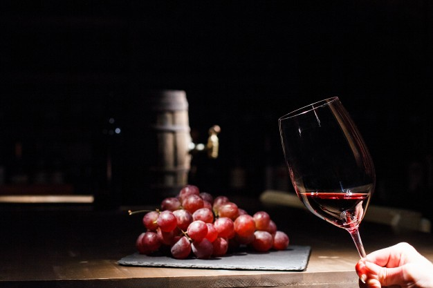 woman-holds-glass-wine-before-bunch-grape-lying-black-plate_1304-2851